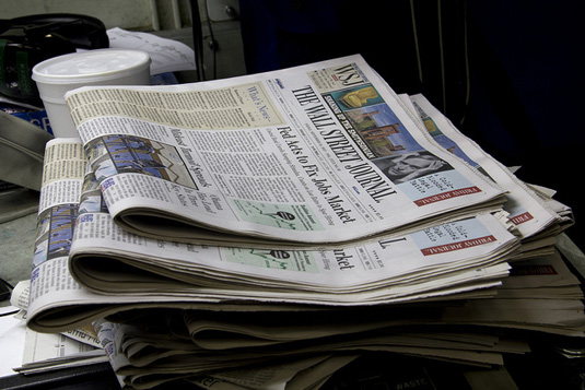 how to generate media buzz for a small business stack of newspapers