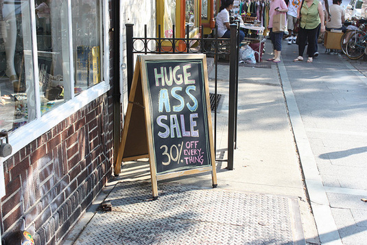 Small business storefront with sale sign in front window